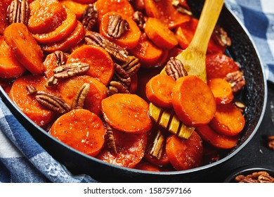 Candied sweet potatoes with brown sugar, maple syrup, orange juice and pecan nuts in a skillet with wooden spatula, horizontal view from above, close-up