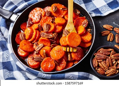 Candied sweet potatoes with brown sugar, maple syrup, orange juice and pecan nuts in a skillet on a concrete table with a kitchen towel, view from above, close-up