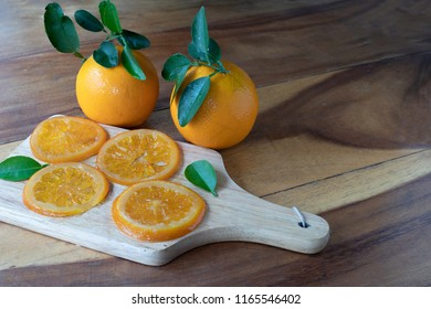 Candied valencia orange slices, candied navel orange slices on a piece of wood which wooden table