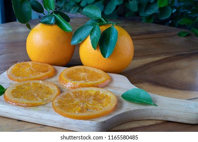Candied valencia orange slices, candied navel orange slices on a piece of wood which wooden table/selective focus