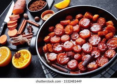 candied yams, sweet potatoes cooked with cinnamon, brown sugar and butter in a black ceramic dish. ingredients on a slate board on a concrete table,  horizontal view from above