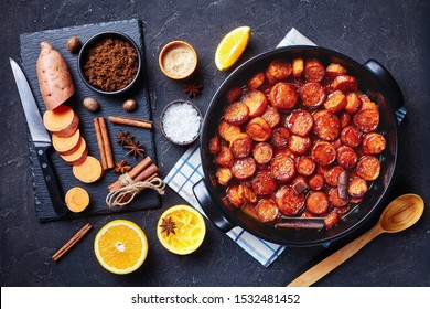 candied yams, sweet potatoes cooked with cinnamon, brown sugar and butter in a black ceramic dish. ingredients on a stone board on a concrete table,  horizontal view from above, flat lay