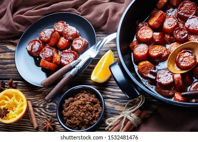 candied yams, sweet potatoes cooked with cinnamon, orange juice, brown sugar and butter in a black ceramic dish. a portion served on a black plate on a rustic wooden table,  horizontal view from above