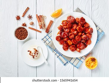 candied yams, sweet potatoes cooked with cinnamon, orange juice, brown sugar and butter served on a white plate on a wooden table with vanilla ice cream, horizontal view from above, flatlay