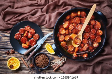 candied yams, sweet potatoes cooked with cinnamon, brown sugar and butter in a black ceramic dish. a portion served on a black plate on a rustic wooden table,  horizontal view from above, flat lay