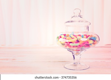 Candies in candy jar on wood table.