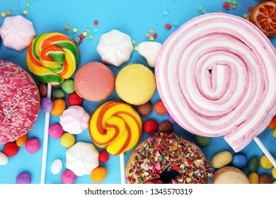 candies with jelly and sugar. colorful array of different childs sweets and treats on blue background