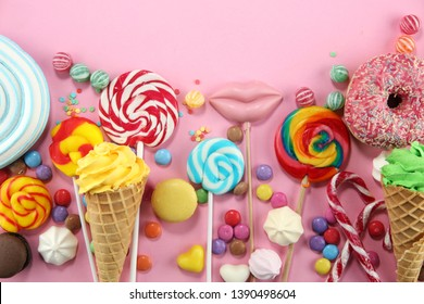 candies with jelly and sugar. colorful array of different childs sweets and treats on pink background