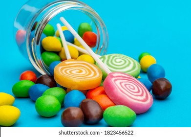 Candies scattered from glass jar on blue background. Close up.