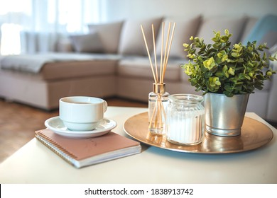 Candle and aromatic reed freshener on table in spa salon. aroma liquid in glass bottle with reed sticks. aroma Diffuser In Luxury in bedroom. Hygge. Scandinavian home decor candles, fragrance, books