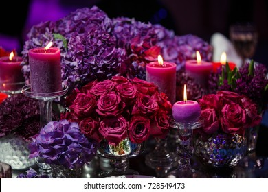 Candle and beautiful flowers on the wedding table.
