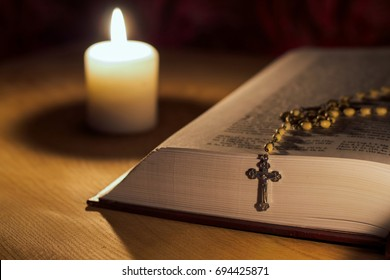 A candle, a bible and a cross a rosary on a wooden table