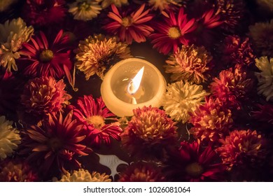 Candle in a bowl full of flowers