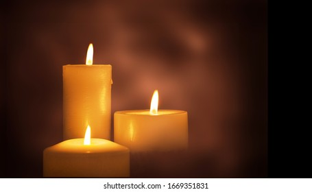 Candle bright flame on a dark background.