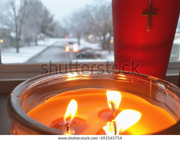 A candle burns before a wintery background.