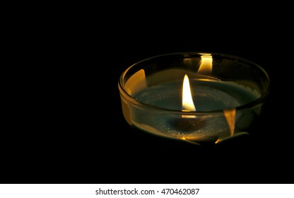 The candle burns in a bowl on dark background