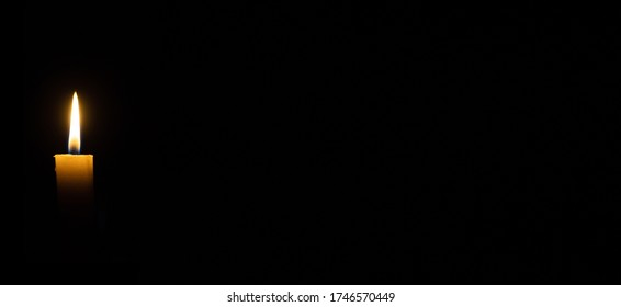 A candle burns in the darkness, copy space. A lit white candle on a black background. The symbol of the eternal memory, mourning, moment of silence, day of remembrance, of loss. Banner or site header.
