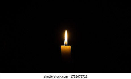 A candle burns in the darkness, copy space. A lit white candle on a black background. Symbol of eternal memory, mourning, minutes of silence, memorial day. The concept of loss and to the memory.