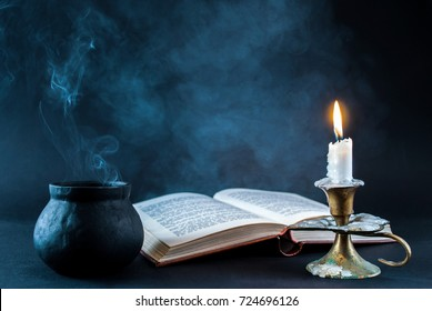 Candle in candlestick burning and smoky pot and old open book on dark and smoked background. Halloween concept