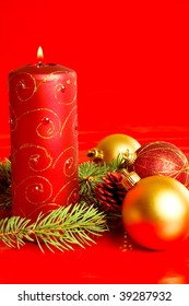 A candle and Christmas decoration on red background