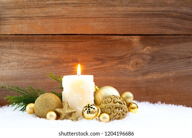 candle and christmas decorations in snow before wooden background, christmas concepts
