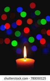 A Candle with Christmas Light Bokeh