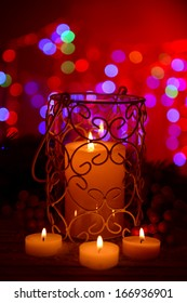 Candle and Christmas tree bud on wooden table on bright background background