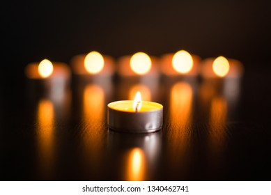 Candle close-up on the background of blurred burning candles