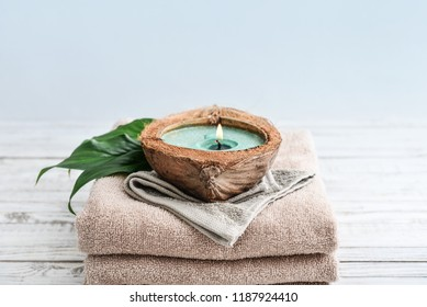 Candle in coconut shell on stack of towels on light background. Spa concept.