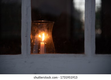 Candle in Colonial window under glass