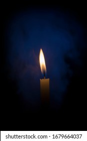 A candle in the dark with soft smoke.