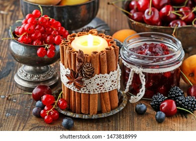 Candle decorated with cinnamon sticks among autumn fruits and flowers.