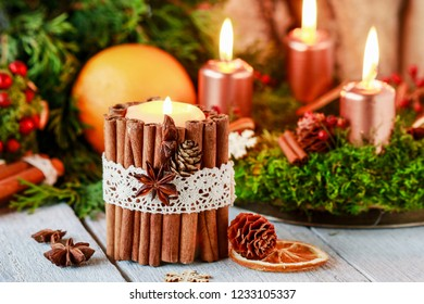Candle decorated with cinnamon sticks. Christmas arrangement.