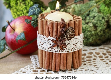 Candle decorated with cinnamon sticks. Christmas table decoration.