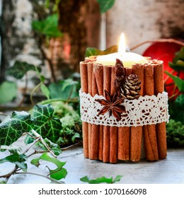 Candle decorated with cinnamon sticks, moss, ivy leaves - beautiful natural Christmas arrangement.