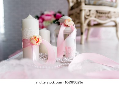 Candle are decorated with pink bow, ribbon and greens stand on the festive table newlyweds covered with a tablecloth. flat lay. top view. Wedding inspiration. Close up. Artwork. Decor. Details.
