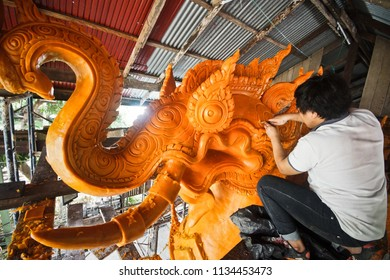 Candle festival in Thailand - man carving a wax candle as the image of the mythical creature