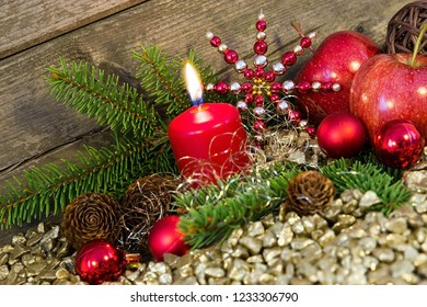 Candle with fir branches and christmas decorations in front of a wooden background