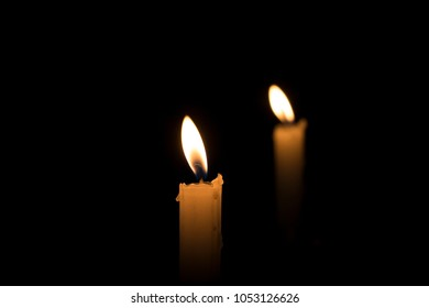 Candle fire with reflection on a black background