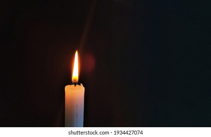 A candle flame burning in darkness