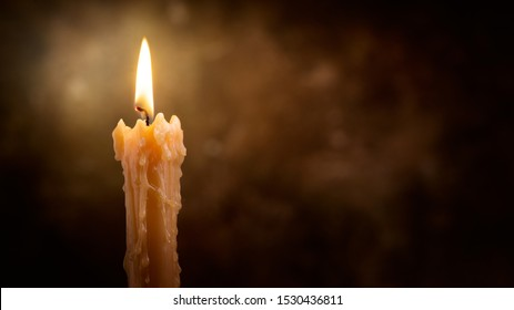 Candle flame close up on a dark background. Melted Wax Candle light border design. Burning at Night, Darkness. Candlelight. Widescreen