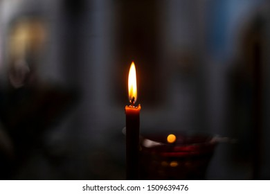 Candle flame inside a church. Fire from a wax candle. Flames illuminate the darkness. The wick burns in a dimly lit room.