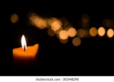 Candle flame light at night with bokeh on dark background