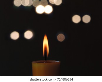Candle flame light at night with bokeh lights on dark background.