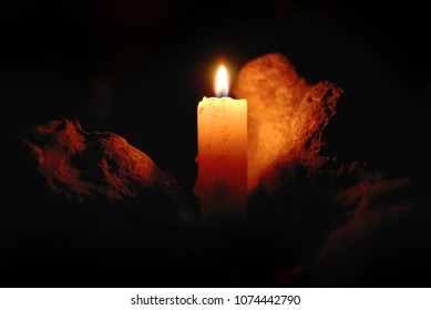 Candle flame with light reflected on a stone