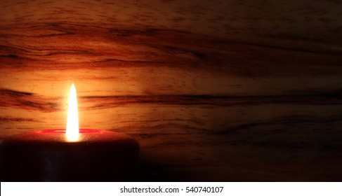 Candle with Flame on Wood Background - photograph of a lit red candle with the flame against a wood grain background.  Selective focus on the candle. Space for text.