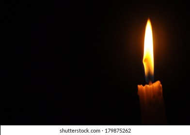Candle With Flame And Space For Caption Over Dark Background  (Noise Visible Due To Low Light Condition)