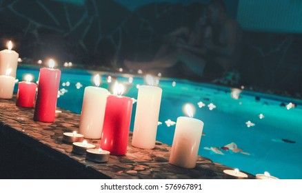 Candle float on water, Romantic evening with red and white candles and light bulb for couples in love or spa. Romantic mood. Valentine's Day. Pool with candles and rose petals floating on water