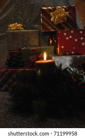Candle in front of Christmas gifts
