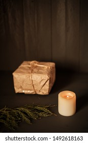 A candle with gift package wrapped in kraft paper in the background